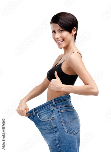 Slender woman wearing enormous jeans, isolated on white