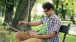 Young happy man with laptop relaxing in park, steadicam shot
