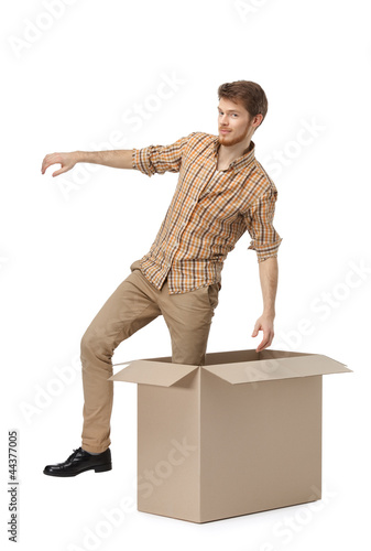 Young man gets out of the cardboard