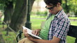 Young happy man reading book in the park, steadicam shot