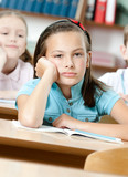 Sad beautiful schoolgirl sits at the desk and leans on her hand