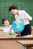 Geography teacher shows something to the pupil at the globe poster