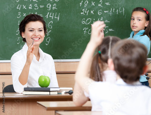 Beautiful teacher questions pupils at algebra