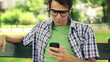 Happy young man using smartphone in park, steadicam shot