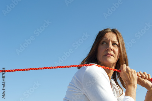 Woman pulling rope sky background
