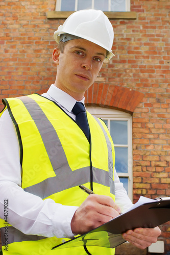 Construction professional with clipboard, an inspector, surveyor