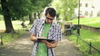 Young man with tablet computer in park, steadicam shot