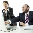 beard business man brunette woman at desk point laptop