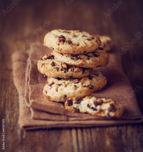 Stacked chocolate chip cookies on brown napkin