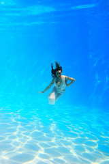 Woman wearing a white dress underwater