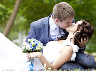 Young couple groom and bride kissing.