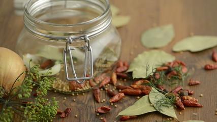 Gewürze und Gurken fallen in Einweckglas