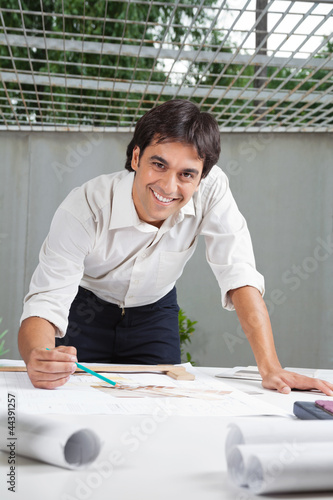 Male Architect Working On Blueprint