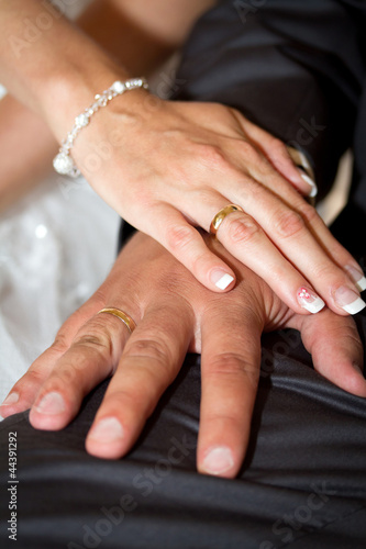 Married couple holding hands together with wedding rings