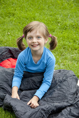 little girl on sleeping bag - camping concept