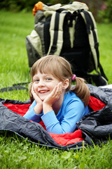 little girl resting in a sleeping bag - camping concept
