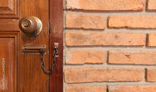 wooden door with locker and red brick