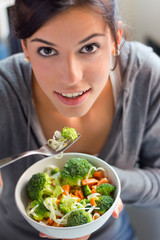 young beautiful woman eating salad at home