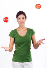 young woman practicing juggling with two apples