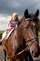 young girl on big brown horse