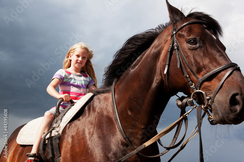blond girl on brown horse