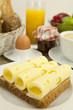 Frühstück mit toast, käse, ei und früchten auf einem Tisch