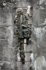 Young soldier with gun climbing