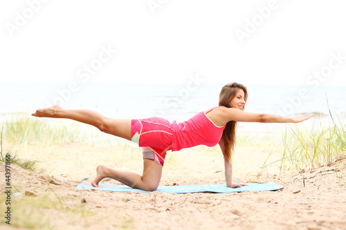 Woman doing yoga exercises on the seaside