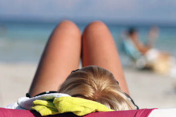 Blond woman sunbathing on beach