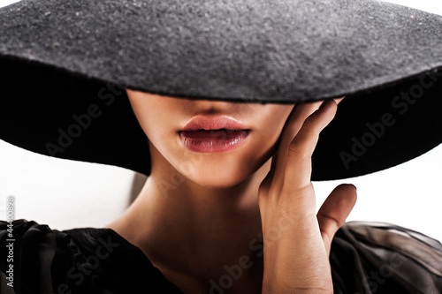 girl in black hat touching face and lips - 44400898