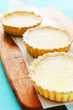 Baked sweet treats lemon tarts on wooden board