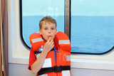 Boy dressed in life jacket blows whistle and stands near window