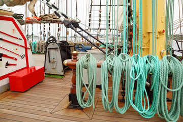 Many ropes, windlass and rigging on an ship with wooden deck
