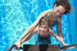 mother and daughter stand on stairs in pool with blue water