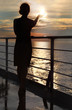dark silhouette of woman holding sun and standing on deck