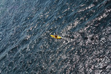 Man rows oar in little yellow kayak floats on open sea