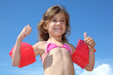 little happy girl with red inflatable armbands thumbs up