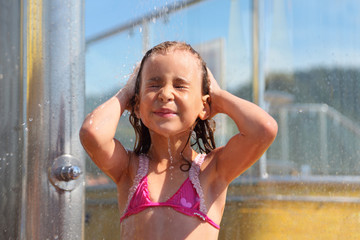 Little girl dressed in swimsuit  takes shower after swimming