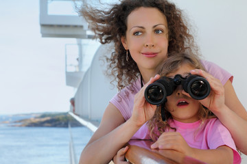 happy mother and daughter stand on ship board and surprised girl