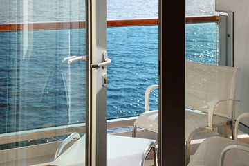 open door; glassy balcony with white chairs and table on liner