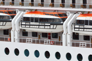 White lifeboats installed on large white passenger liner board