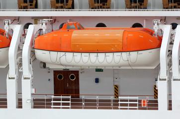 Orange lifeboat installed on large white passenger liner deck