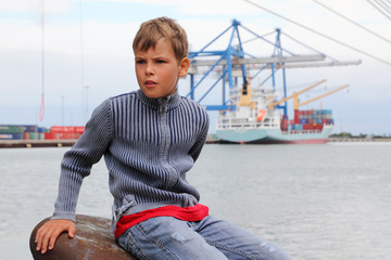 boy sits on stone and looks into distance at background of ship