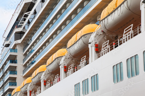 Row of lifeboats installed on beautiful white passenger liner