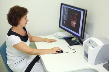 Dentist carefully looks skull X-rays at computer monitor