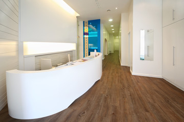 Lit reception area in dental clinic. Empty workplace with table