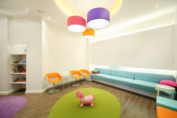 Empty lit room with soft couches, chairs and toys for children