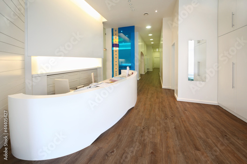 Leinwanddruck Bild Lit reception area in dental clinic. Empty workplace with table
