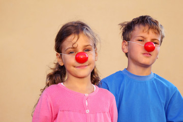 Brother and sister with red clown noses stand near wall