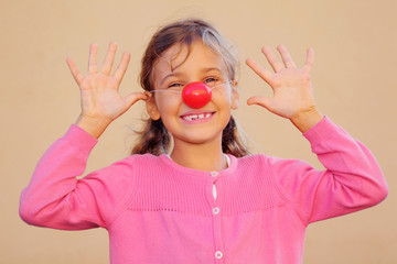 Beautiful girl wearing pink blouse with red clown nose smiles